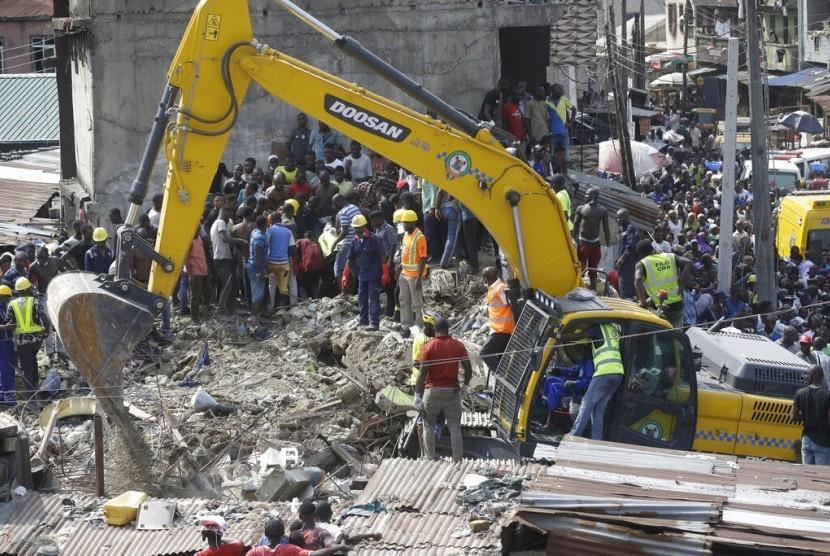 Petugas darurat mencari korban yang terjebak dalam bangunan ambruk di Lagos, Nigeria, Rabu (13/3). Lebih dari 100 anak sekolah dasar tertimbun bangunan.