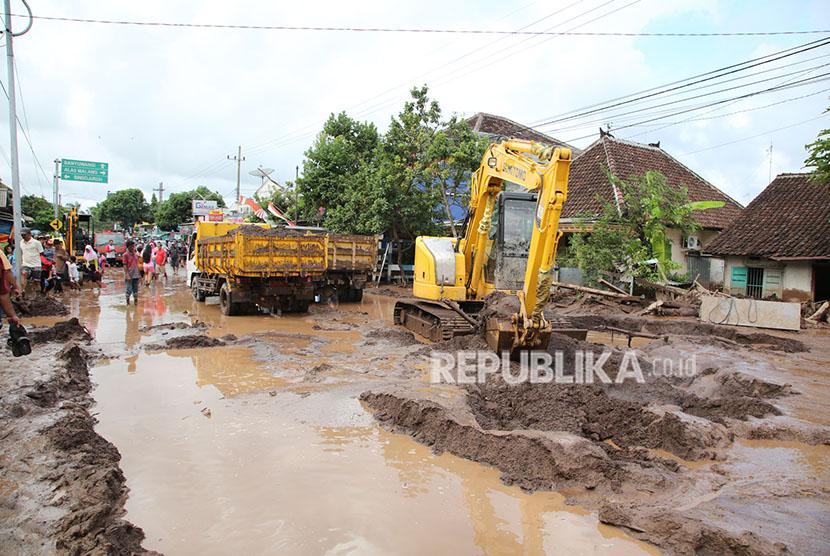 Petugas dengan alat berat membersihkan lumpur akibat banjir bandang yang melanda Banyuwangi, Jawa Timur, Jumat (22/6).