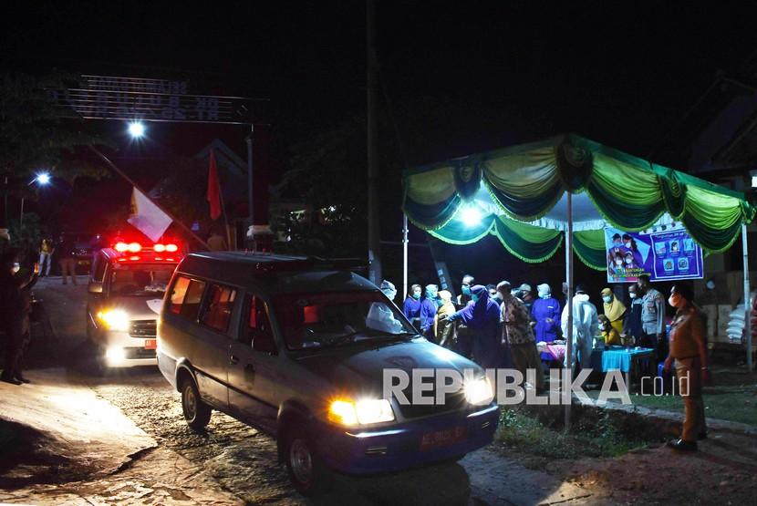 Madiun Evakuasi 89 Warga Klaster Hajatan ke RSUD Dolopo. Petugas dengan menggunakan mobil ambulans bersiap menjemput warga yang dinyatakan positif COVID-19 di Desa Bantengan, Wungu, Kabupaten Madiun, Jawa Timur, Senin (14/6/2021) malam. Pemkab Madiun mengerahkan 25 unit mobil ambulans untuk menjemput 88 warga positif COVID-19 dari klaster hajatan pernikahan di desa tersebut untuk dibawa ke rumah sakit guna mendapatkan perawatan.