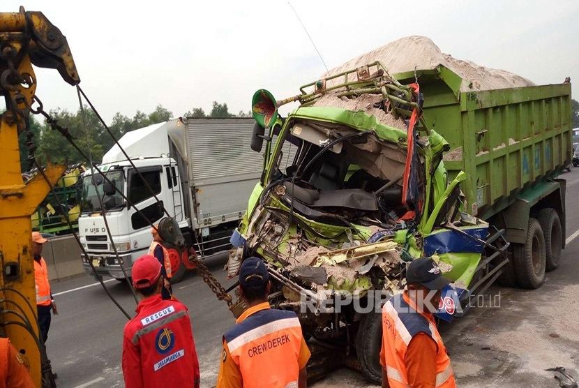 Petugas derek PT Jasa Marga mengevakuasi truk pengangkut pasir di Tol Cikampek-Jakarta Km 40 arah Cikampek, Jumat (12/2). (Republika/Yogi Ardhi)