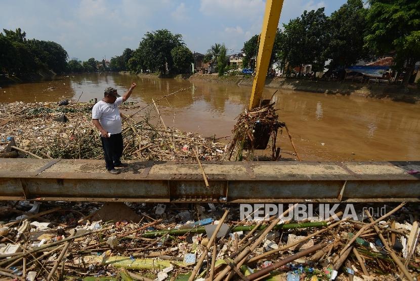 Petugas dibantu alat berat mengangkut sampah yang mengendap di Sungai Ciliwung Kawasan Kampung Melayu, Jakarta Timur, Ahad (3/4). (Republika/Raisan Al Farisi)