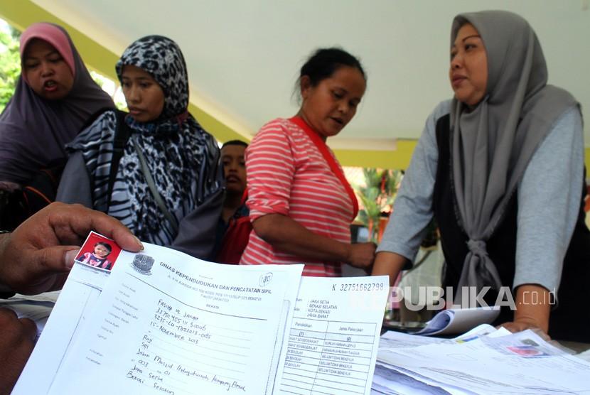 Petugas Dinas Kependudukan dan Catatan Sipil melayani pemohon pembuatan Kartu Identitas Anak (KIA), di Kantor Kecamatan Bekasi Selatan, di Bekasi, Jawa Barat, Rabu (19/12/2018).