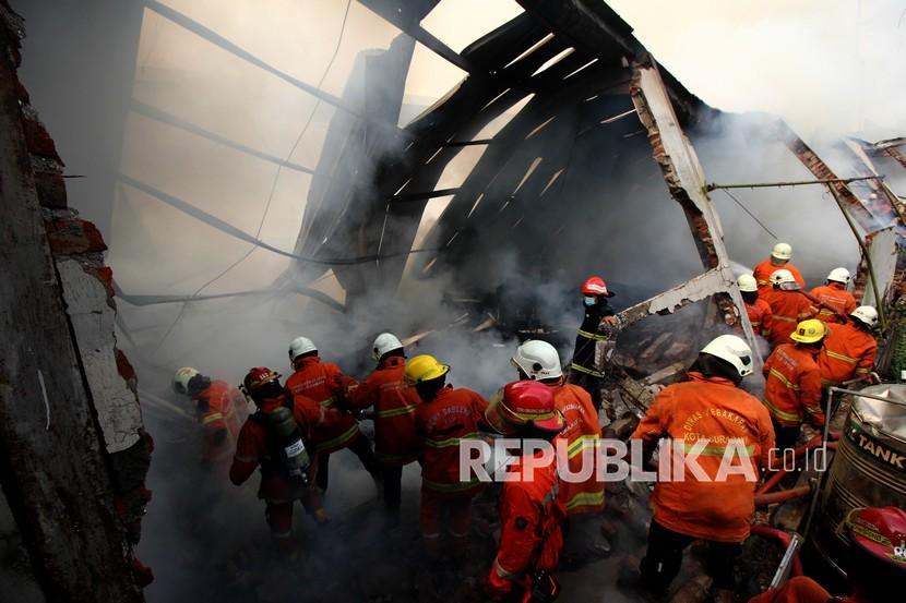 Petugas Dinas Pemadam Kebakaran Kota Surabaya melakukan pembasahan gudang yang terbakar di Jalan Simorejo Sari B, Surabaya, Jawa Timur, Selasa (27/10/2020). Sebanyak 22 unit kendaraan pemadam kebakaran dikerahkan untuk memadamkan gudang mebel yang ludes terbakar itu.