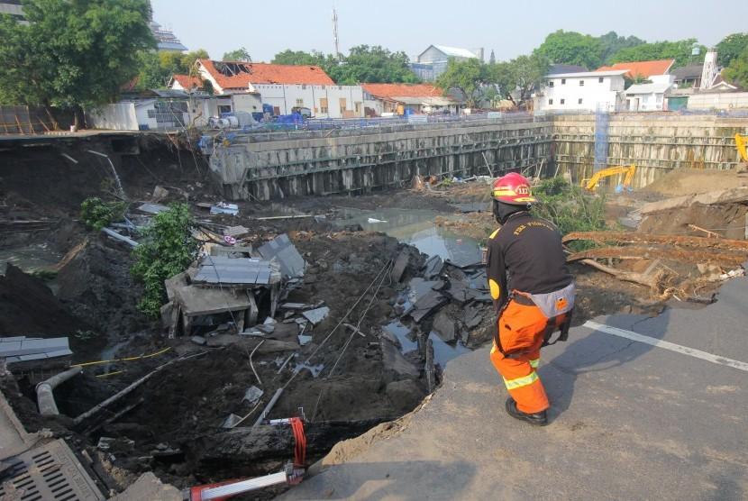 Petugas Dinas Pemadam Kebakaran Kota Surabaya memeriksa lokasi tanah ambles di Jalan Raya Gubeng, Surabaya, Jawa Timur, Rabu (19/12/2018).