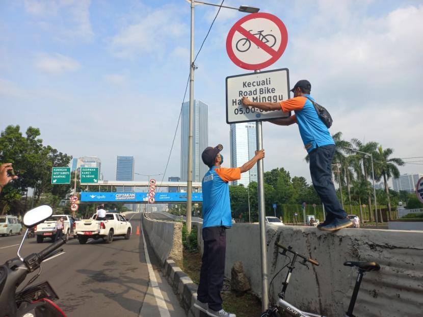Petugas Dinas Perhubungan DKI Jakarta mencopot rambu yang mengecualikan pengguna sepeda road bike (sepeda balap) di Jalan Layang Non-Tol Kampung Melayu-Tanah Abang alias JLNT Casablanca, kawasan Tebet, Jakarta Selatan, Ahad (13/6). Pencopotan dilakukan setelah adanya protes dari koalisi LSM.