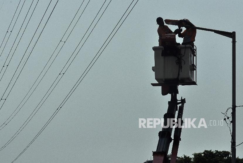 Petugas Dinas Perindustrian dan Energi mengganti lampu penerangan jalan umum (PJU) di kawasan Jalan Kali Sekretaris, Jakarta Barat, Senin (21/8).