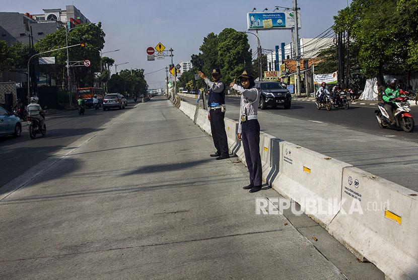 Petugas Dishub DKI Jakarta mengatur lalu lintas saat uji coba penutupan tiga simpang di kawasan Jalan Mampang Prapatan Raya, Jakarta, Sabtu (19/5).