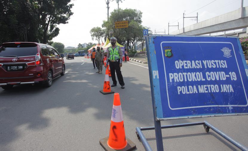 Petugas gabungan berjaga saat penyekatan larangan mudik lebaran 2021 di perbatasan pos pemeriksaan sekitar Pasar Jumat, Lebak Bulus, Jakarta, Rabu (12/5/2021).