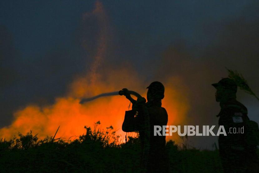 Petugas gabungan dari BPBD Kab Ogan Ilir (OI), Manggala Agni Daops Banyuasin, TNI dan Polri melakukan pemadaman kebakaran lahan di Arisan Jaya, Ogan Ilir (OI), Sumatera Selatan, Rabu (25/7).