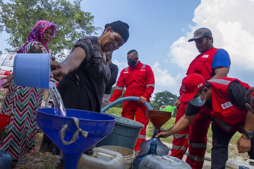 Petugas gabungan dari Palang Merah Indonesia (PMI) mendistribusikan air gratis di Desa Kertasari, Pangkalan, Karawang, Jawa Barat, Sabtu (25/9/2021). PMI bersama Tagana mendistribusikan sebanyak 31 ribu liter air bersih untuk warga yang mengalami kesulitan air bersih sebanyak 595 Kartu Keluarga (KK).