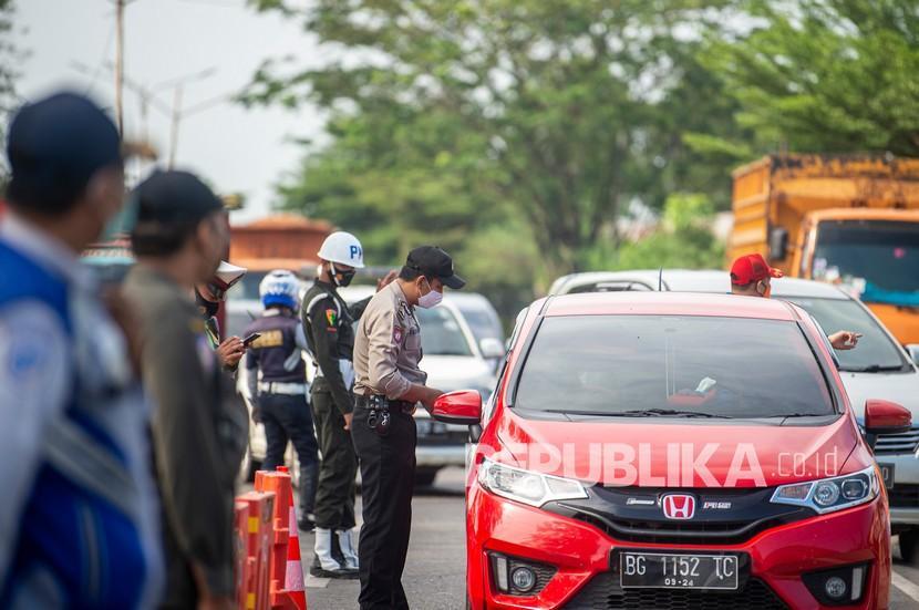 Petugas gabungan dari Polri, TNI, Dishub dan Sat Pol PP memeriksa kendaraan yang melintas di Jalan Lintas Timur Ogan Ilir (OI)-Palembang, Sumatera Selatan, Jumat (7/6/2021). Pemeriksaan tersebut sebagai upaya untuk menyekat masyarakat yang nekat mudik jelang perayaan Hari Raya Idul Fitri 1442 H dari arah Lampung menuju Palembang.