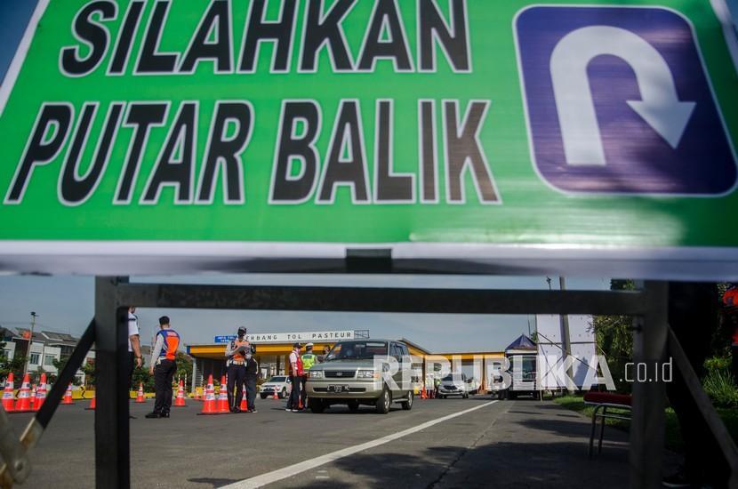 Petugas gabungan melakukan pemeriksaan kelengkapan administrasi pengendara saat penyekatan larangan mudik lebaran di Gerbang Tol Pasteur, Bandung, Jawa Barat, Kamis (6/5). Larangan mudik Lebaran Idul Fitri 2021 mulai berlaku hari ini (6/5) hingga 17 Mei.