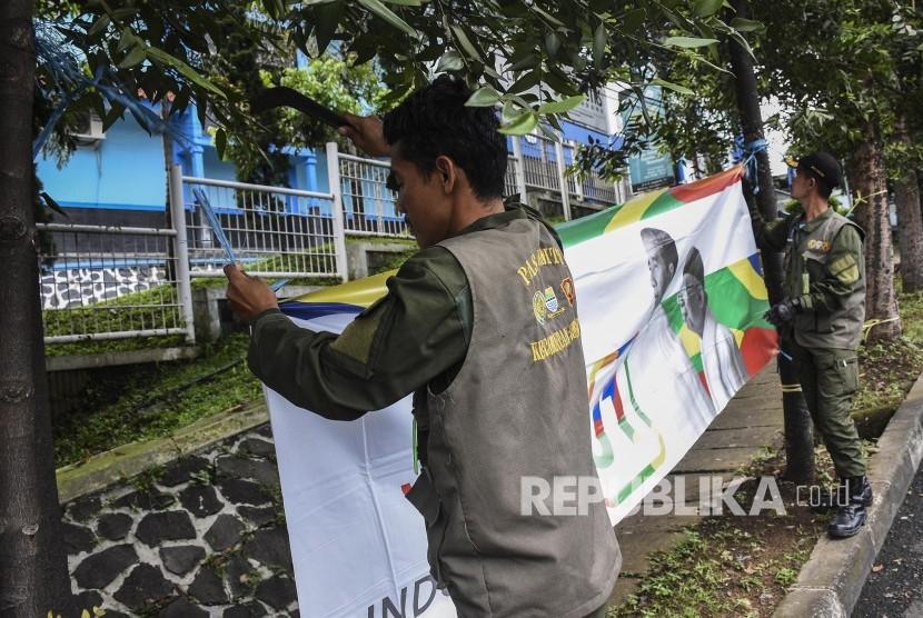 Petugas gabungan mencopot Alat Peraga Kampanye (APK) Pemilu 2019 di Kawasan Jalan Ir H Djuanda, Kota Bandung, Ahad (14/4). Penurunan Alat Peraga Kampanye (APK) P