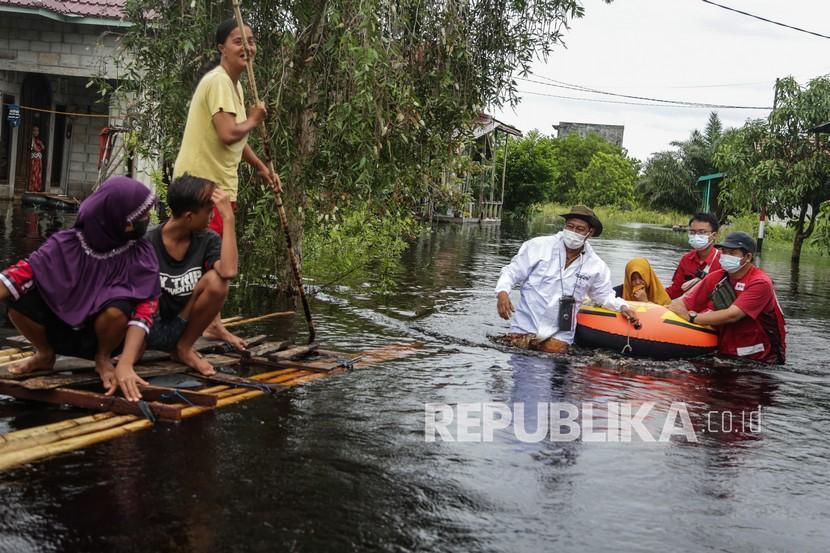 Petugas gabungan mengevakuasi warga terdampak banjir di Jalan Danau Ranggas, Palangkaraya, Kalimantan Tengah, Selasa (21/9/2021). Sebanyak 45 warga terdampak banjir luapan Sungai Kahayan dan Sungai Rungan dievakuasi guna mendapatkan perawatan kesehatan di RS Kota Palangkaraya dan posko pengungsian, karena banjir yang semakin tinggi merendam permukiman warga dalam seminggu terakhir.