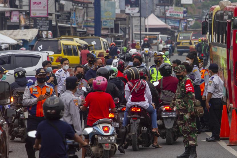 Petugas gabungan menghalau pemudik sepeda motor saat hari pertama penyekatan larangan mudik di Karawang, Jawa Barat, Kamis (6/5/2020). Penyekatan akses transportasi tersebut sebagai tindak lanjut kebijakan larangan mudik Lebaran pada 6 -17 Mei 2021 yang berlaku bagi kendaraan pribadi, angkutan umum dan motor kecuali mobil pemadam kebakaran, angkutan logistik dan kebutuhan pokok serta ambulans.