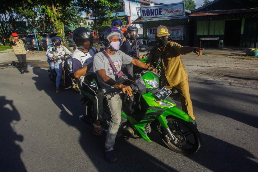 Petugas gabungan menghentikan pengendara yang melanggar protokol kesehatan (prokes) saat Operasi Yustisi di Jalan Diponegoro, Palangkaraya, Kalimantan Tengah, Senin (24/5/2021). Operasi gabungan tersebut untuk menertibkan warga agar lebih disiplin dalam menerapkan protokol kesehatan COVID-19 dan memberikan sanksi administrasi berupa denda Rp100 ribu, sanksi sosial serta tes Antigen secara acak bagi pelanggar prokes.