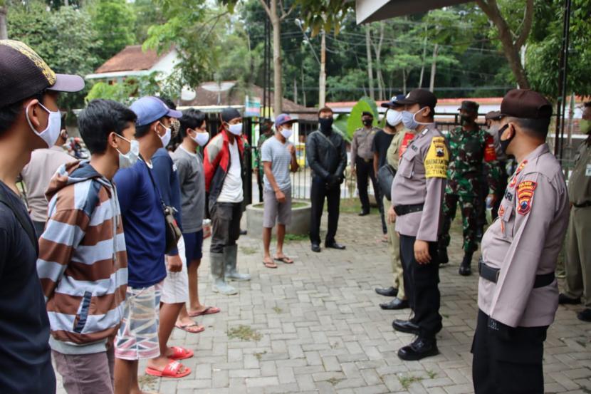 Petugas gabungan operasi yustisi penegakan hukum protokol kesehatan Provinsi Jawa Tengah memberikan sanksi fisik kepada masyarakat yang kedapatan melanggar,