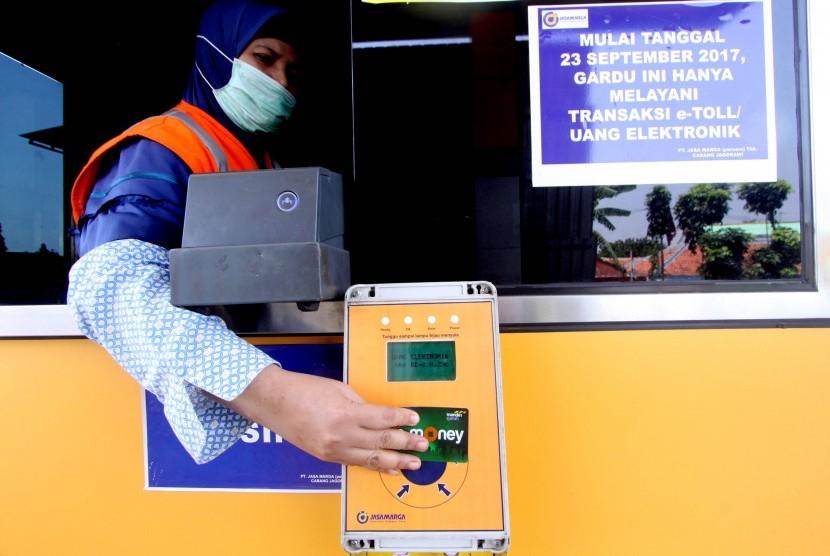 Petugas Jasa Marga membantu pengendara melakukan transaksi nontunai menggunakan e-toll di gerbang tol. ilustrasi