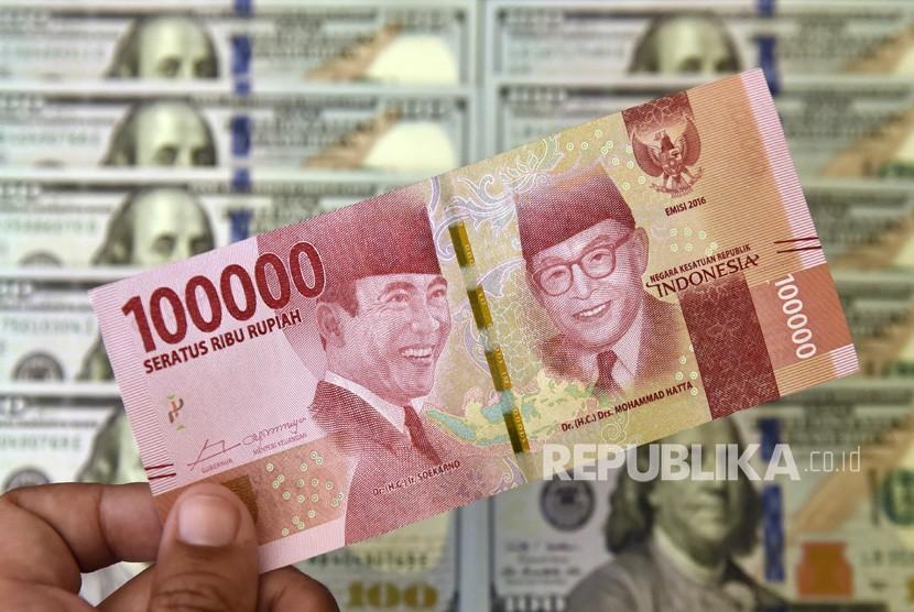 Petugas jasa penukaran valuta asing memeriksa lembaran mata uang rupiah dan dollar AS. ilustrasi