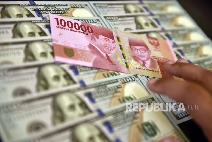 Petugas jasa penukaran valuta asing memeriksa lembaran mata uang rupiah dan dolar AS di Jakarta. ilustrasi