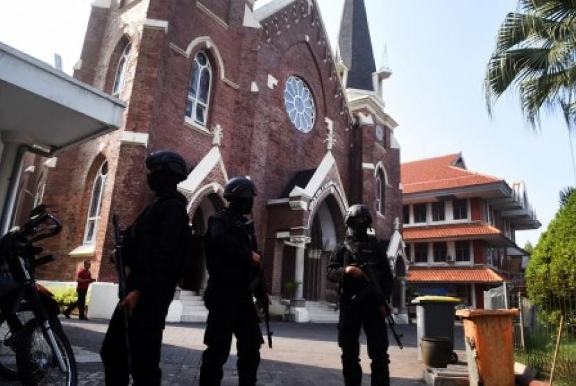 Petugas keamanan berjaga di depan gereja saat misa di Gereja Katolik Kelahiran Santa Perawan Maria, Surabaya, Jawa Timur, Ahad (20/5). Pengamanan tersebut guna mengantisipasi dan memberikan rasa aman kepada jemaat yang melaksanakan kebaktian dan misa sepekan pascaledakan bom di tiga gereja di Surabaya.