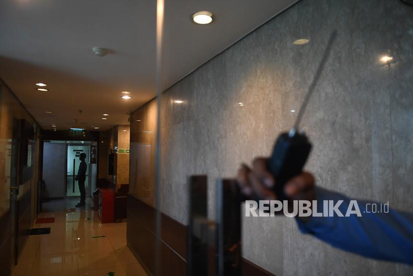 Petugas keamanan berjaga di depan ruangan yang terkena peluru nyasar di Kompleks Parlemen, Senayan, Jakarta, Senin (15/10).