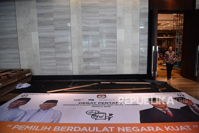 Petugas keamanan melintas di dekat spanduk yang dipersiapkan untuk debat pertama capres-cawapres Pilpres 2019 di Hotel Bidakara, Jakarta Selatan, Rabu (16/1/2019).