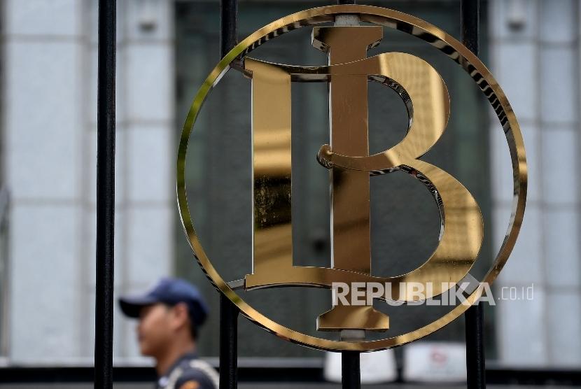 Petugas keamanan melintas didekat logo Bank Indonesia (BI), Jakarta, Ahad (1/10).