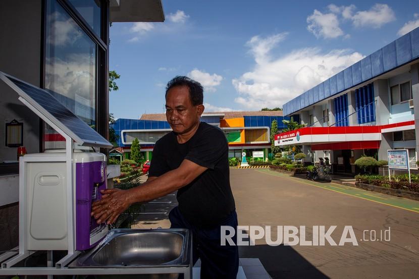 Petugas keamanan mencuci tangan di wastafel kreasi sekolah yang menggunakan tenaga surya di SMKN 26 Rawamangun, Jakarta Timur, Sabtu (30/5/2020). Sejumlah persiapan dilakukan SMKN 26 Rawamangun dalam rangka pelayanan Penerimaan Peserta Didik Baru (PPDB) 2020 dengan standar protokol pencegahan penyebaran COVID-19.