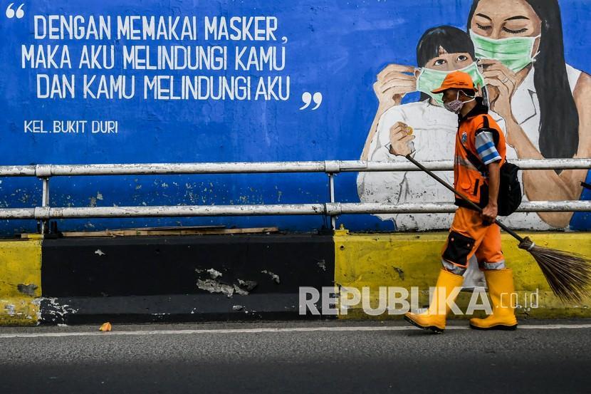 Petugas kebersihan melintas di depan mural tentang pandemi COVID-19 di Kawasan Tebet, Jakarta. Pemerintah didesak melakukan pembatasan yang lebih ketat dari upaya PPKM mikro.