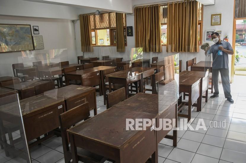 Petugas kebersihan membersihkan akrilik pembatas meja belajar di SMA 81 Jakarta Timur, beberapa waktu lalu.