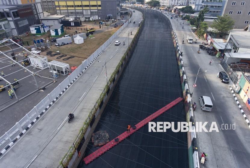 Petugas kebersihan membersihkan sampah di Kali Item yang telah ditutup jaring di dekat Wisma Atlet Kemayoran, Jakarta, Jumat (20/7).