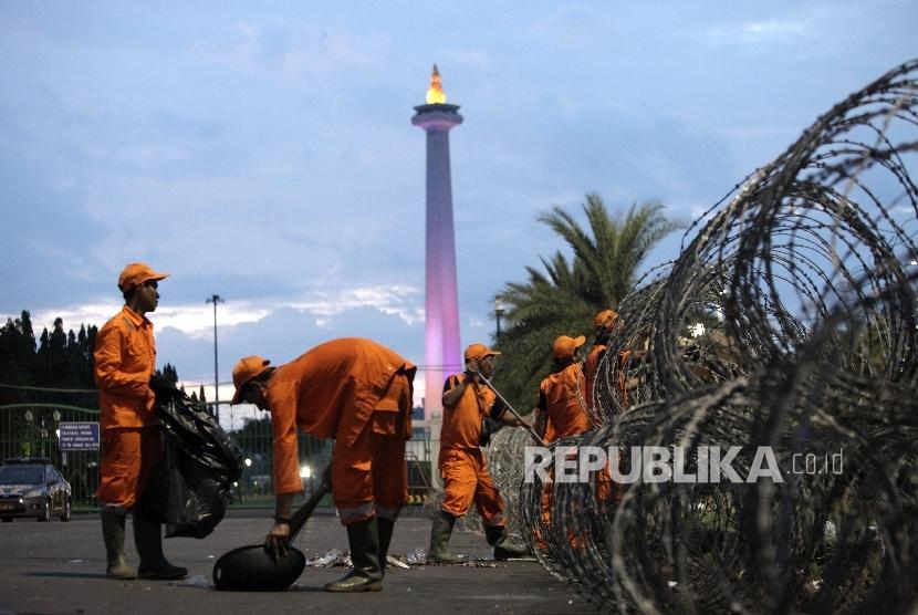 Petugas kebersihan membersihkan sisa sampah warga yang merayakan tahun baru di kawasan Monas, Jakarta Pusat, Ahad (1/1).