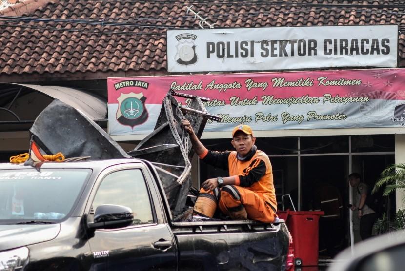 Petugas kebersihan mengangkut barang sisa perusakan dan pembakaran di Polsek Ciracas, Jakarta, Rabu (12/12/2018).