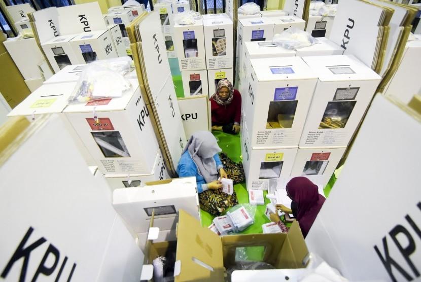 Petugas Kelompok Panitia Pemungutan Suara (KPPS) memeriksa kelengkapan logistik Pemilu sebelum didistribusikan ke kelurahan di gudang logistik KPU Jakarta Pusat, GOR Tanah Abang, Jakarta, Senin (15/4/2019).