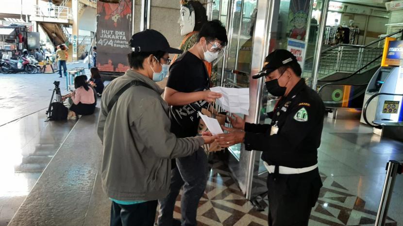 Petugas keamanan mengecek surat vaksinasi yang dibawa pengunjung ketika hendak masuk pintu masuk timur Blok A Pasar Tanah Abang, Jakarta Pusat, Selasa (27/7).