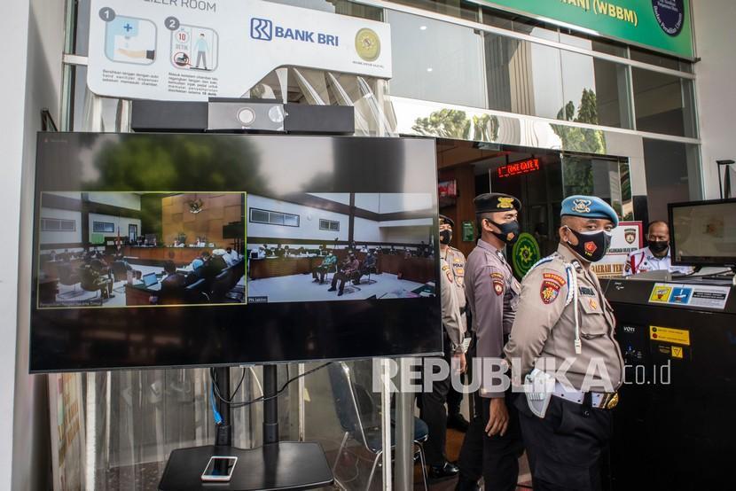 Petugas kepolisian berada di dekat layar yang menampilkan suasana sidang lanjutan kasus pelanggaran protokol kesehatan dengan terdakwa Rizieq Shihab di Pengadilan Negeri (PN) Jakarta Timur, Jakarta, Senin (19/4/2021). Sidang tersebut beragendakan pemeriksaan saksi yang dihadirkan Jaksa Penuntut Umum (JPU).