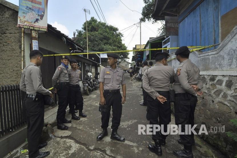 Petugas Kepolisian bergaja saat melakukan memeriksa dan menggeledah sebuah rumah terduga teroris oleh tim Densus 88 di Kampung Paledang, Kecamatan Cileunyi, Kabupaten Bandung, Selasa (6/6).
