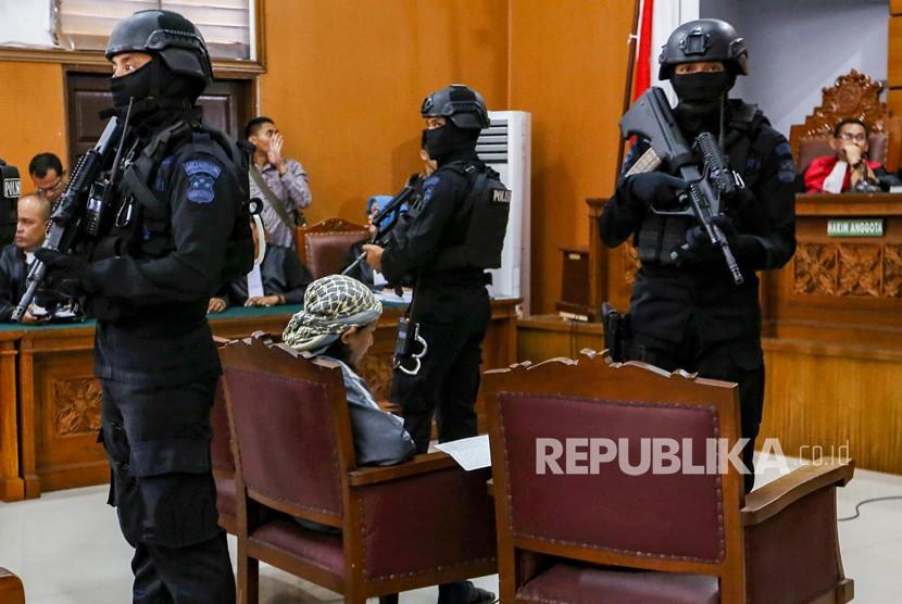 Petugas kepolisian bersenjata lengkap menjaga terdakwa kasus dugaan serangan teror bom Thamrin dengan terdakwa Oman Rochman alias Aman Abdurrahman saat menjalani sidang lanjutan di Pengadilan Negeri Jakarta Selatan, Jumat (25/5).