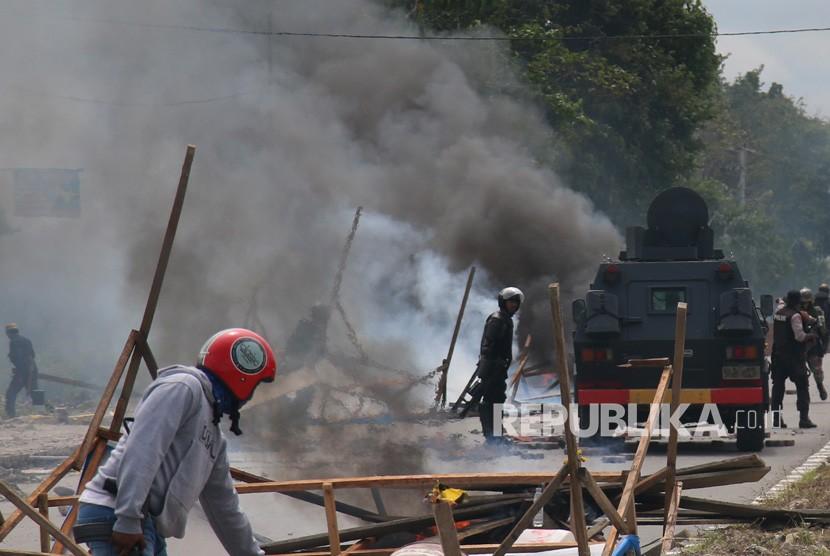 Petugas kepolisian dan TNI melakukan penjagaan saat massa aksi menutup jalan di Mimika, Papua, Rabu (21/8/2019).