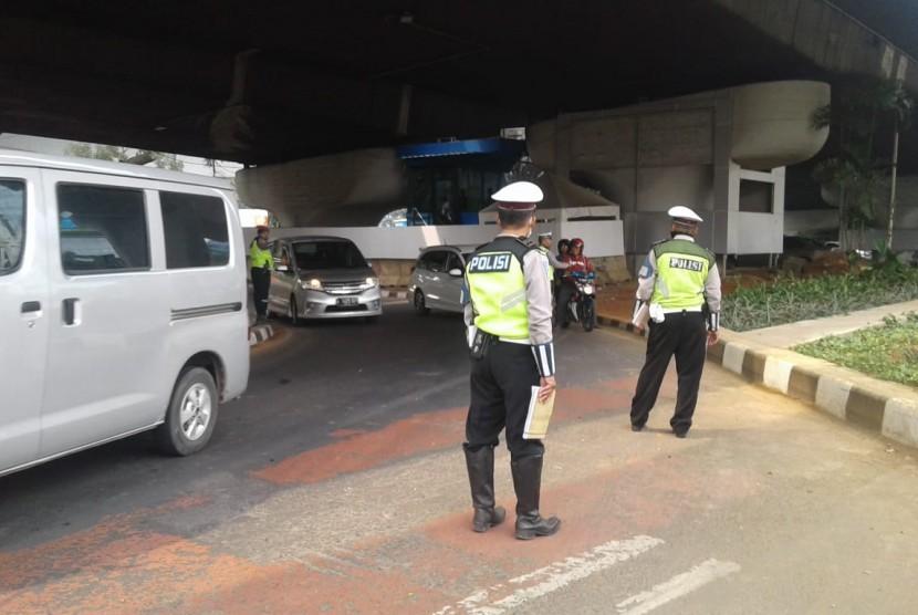 Petugas kepolisian melakukan operasi ganjil-genap di kawasan Pancoran, Jakarta Selatan, Rabu (1/7). Hingga siang hari, telah lebih dari 200 surat tilang dikeluarkan.