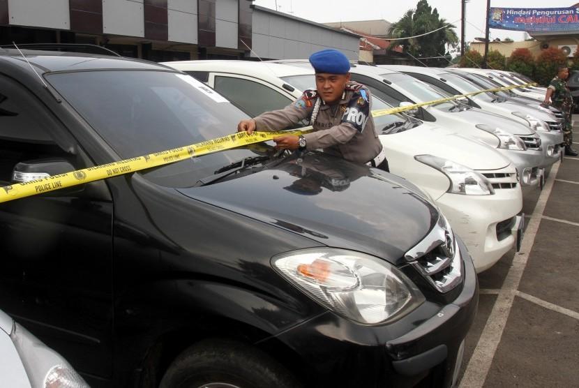 Petugas kepolisian memasang garis polisi pada mobil barang bukti hasil pencurian kendaraan bermotor di Mapolres Kota Depok, Jawa Barat, Rabu (25/5).