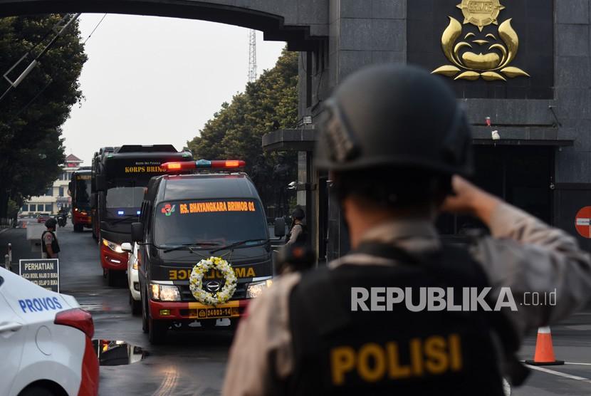 Petugas kepolisian memberi hormat saat mobil yang mengangkut jenazah anggota Brimob korban penikaman, Bripka Marhum Prencje di bawa menuju rumah duka dari Mako Brimob Kelapa Dua, Depok, Jawa Barat, Jum'at (11/5).