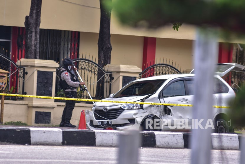 Police officers search the minivan used by suspected terrorists to attack Riau Police Headquarters in Pekanbaru, Riau, on Wednesday (May 16).