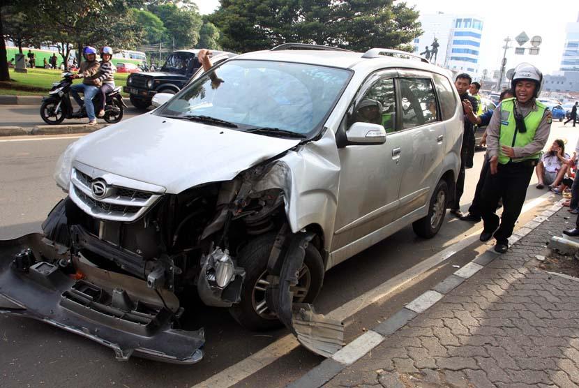 Petugas Kepolisian mengamankan mobil yang mengalami kecelakaan tunggal di Jalan Raya (ilustrasi).