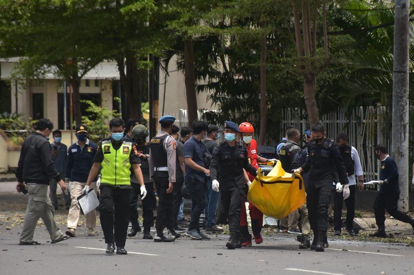 Petugas kepolisian mengangkat kantong jenazah berisi bagian tubuh dari terduga pelaku bom bunuh diri di depan Gereja Katedral Makassar, Sulawesi Selatan, Ahad (28/3/2021). Bagian tubuh jenazah tersebut selanjutnya dibawa ke Rumah Sakit Bhayangkara Makassar untuk diidentifikasi.
