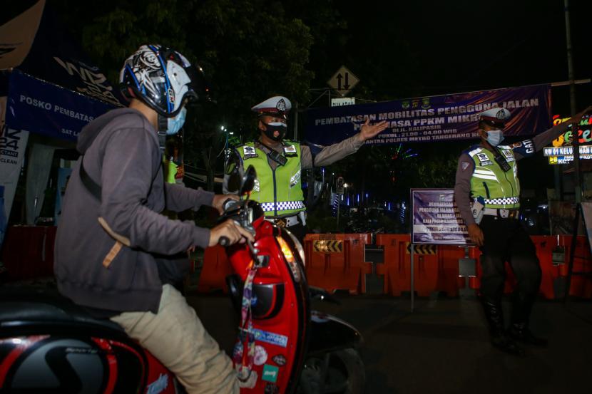 Petugas kepolisian mengarahkan pengendara saat akan melintas di area jalan yang ditutup untuk membatasi mobilitas warga di Jalan Kali Pasir, Kota Tangerang, Banten, Kamis (24/6/2021). Pembatasan tersebut dilakukan mulai pukul 21.00 WIB hingga 04.00 WIB di titik rawan keramaian di Kota Tangerang guna menekan penyebaran COVID-19.