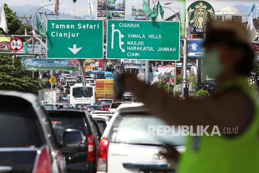 Petugas kepolisian mengatur kendaraan menuju puncak yang terjebak kemacetan di Simpang Gadog, Bogor, Jawa Barat, Jumat (6/5). (Republika/Rakhmawaty La'lang)