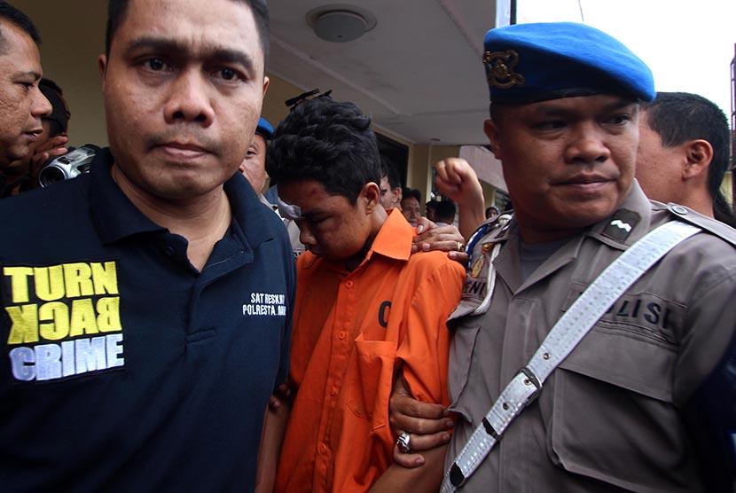 Petugas kepolisian mengawal seorang tersangka kasus pembunuhan Roy Mando Sah Siregar (20) saat gelar kasus di Mapolresta Medan, Sumatera Utara, Selasa (3/5).