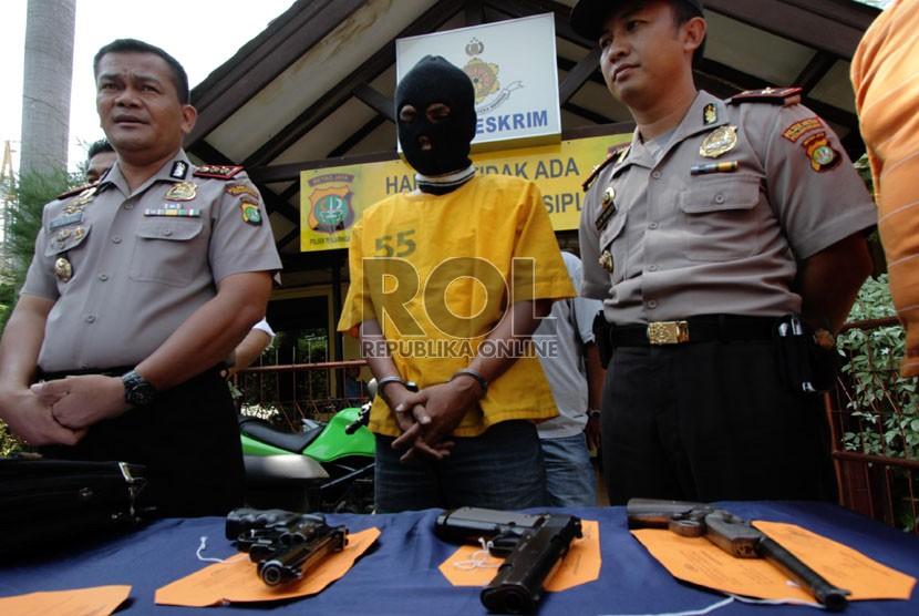 Petugas kepolisian menunjukkan barang bukti dan tersangka pada rilis tindak pidana menyimpan dan kepemilikan senjata api rakitan
